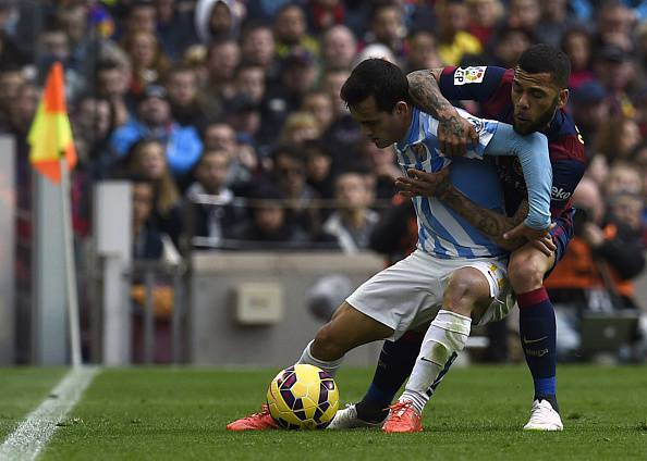 Barcelona's Brazilian defender Dani Alves (R) vies with Malaga's Argentinian midfielder Pablo Javier Perez (L) and Malaga's midfielder Sergi Darder (L) during the Spanish league football match FC Barcelona vs Malaga CF at the Camp Nou stadium in Barcelona on February 21, 2015. AFP PHOTO / LLUIS GENE        (Photo credit should read LLUIS GENE/AFP/Getty Images)
