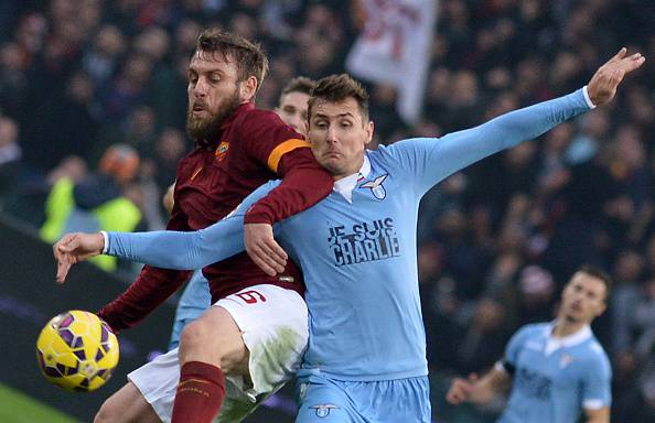 Roma's forward Daniele De Rossi (L) vies with Lazio's forward from Germany Miroslav Klose during the Italian Serie A football match AS Roma vs Lazio on January 11, 2015 in Rome.  AFP PHOTO / TIZIANA FABI        (Photo credit should read TIZIANA FABI/AFP/Getty Images)