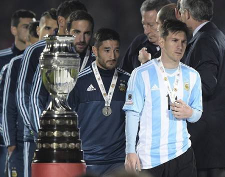 Argentina's forward Lionel Messi (R) walks off the podium after receiving the second-place medal after losing to Chile in a penalty shootout at the end of the 2015 Copa America football championship final against Argentina, in Santiago, Chile, on July 4, 2015. Chile won 4-1 (0-0). AFP PHOTO / JUAN MABROMATA        (Photo credit should read JUAN MABROMATA/AFP/Getty Images)